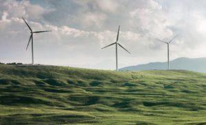 Windkraftanlagen auf grünem Feld beim Produzieren von Ökostrom