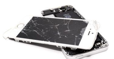 Zerbrochenes weißes Handy mit Handyversicherung auf weißem Untergrund